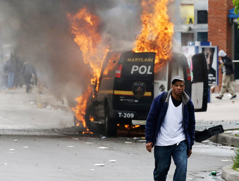 Image: A man walks past a burning police vehicle